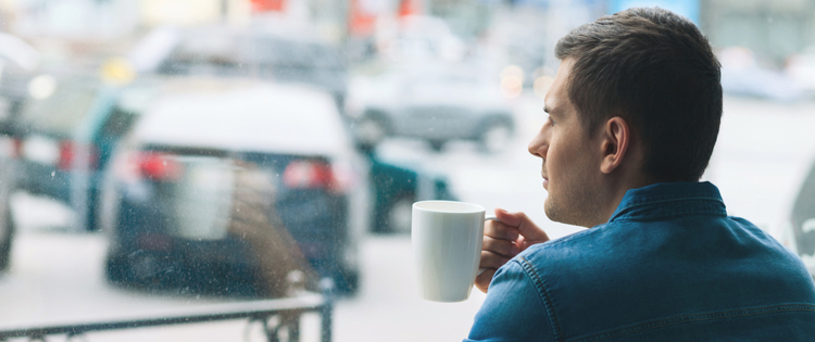 Man drinking coffee looking out window