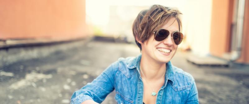 Photo of a woman wearing aviator sunglasses. She's sitting in an alley.