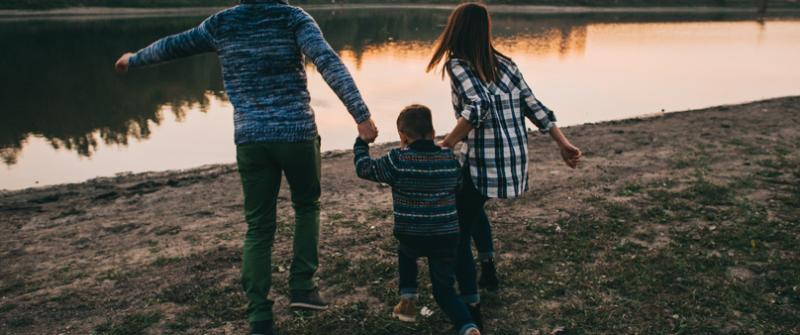 Photo of two adults with a child, walking towards a river and holding hands