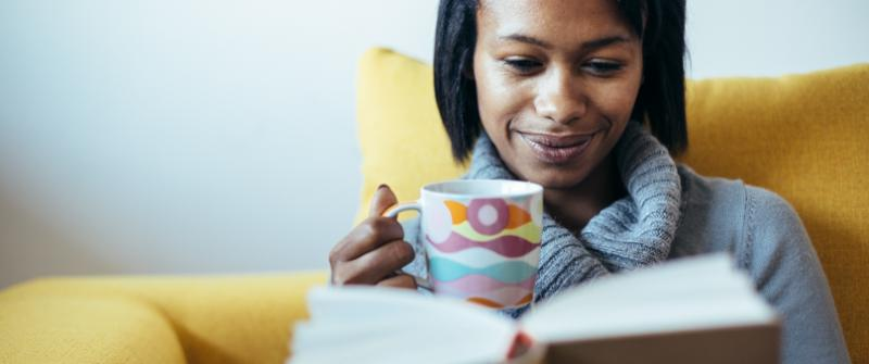 Photo of a woman reading a book with a mug of tea. She's sitting in a yellow chair.
