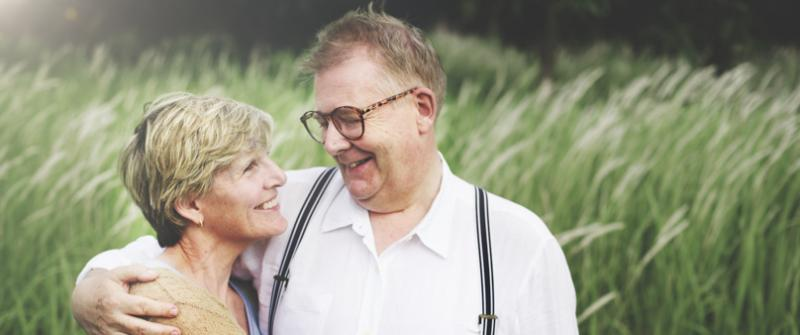 Photo of a couple standing together in a field smiling at one another, a man with his arm around the woman