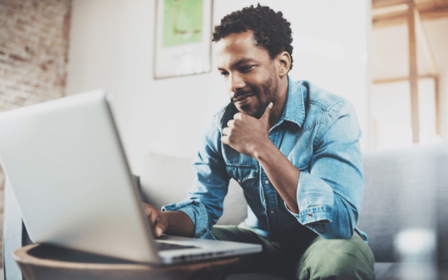 Photo of a black man looking at his laptop while sitting on a couch