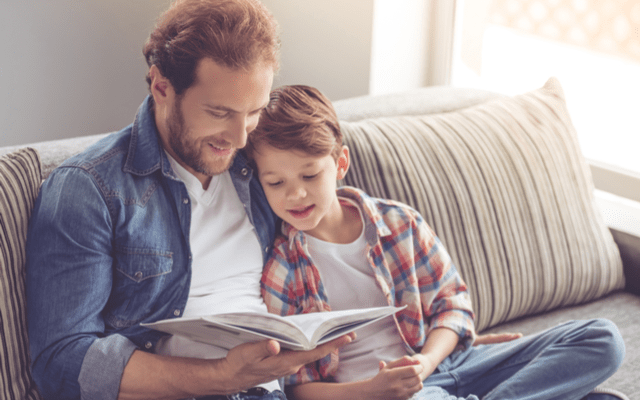 Photo of a man and his young son reading a book together on a sofa