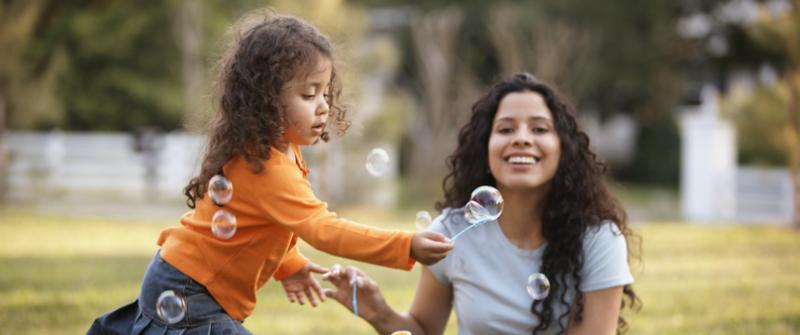 Photo of a mom helping her daughter blow bubbles in the park.