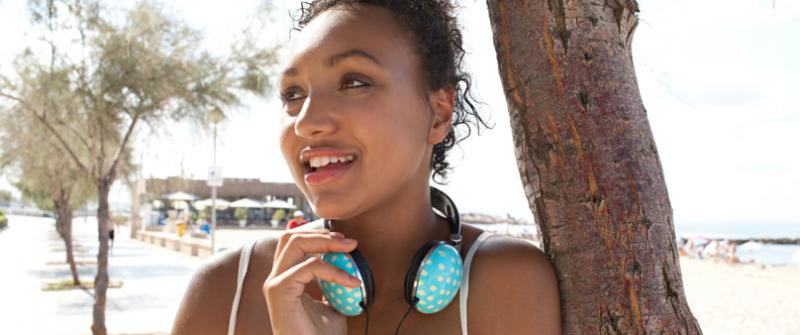 Photo of a smiling young woman leaning against a tree. She has polka dot headphones around her neck.