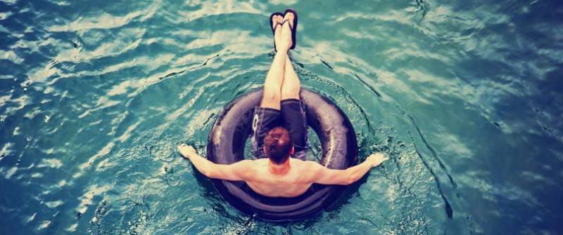 Photo of a man floating on an inner tube.