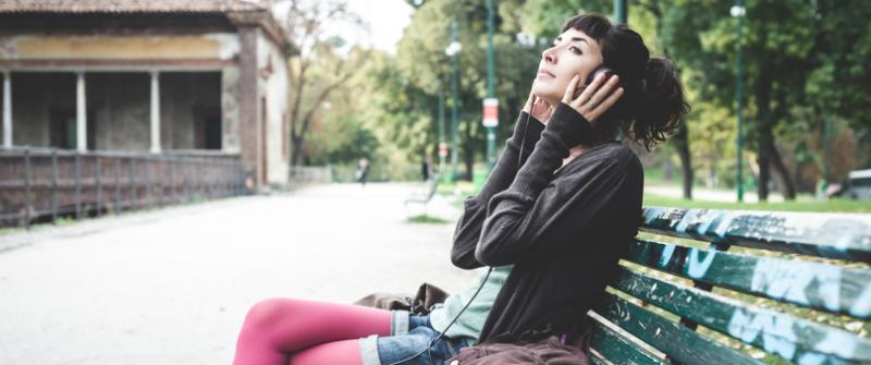 Photo of a woman sitting on a city park bench wearing headphones. Her hands are by her ears, gently pressing the headphones tighter.