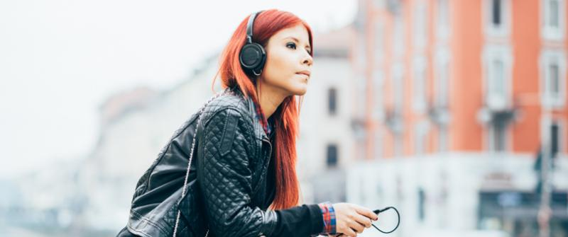 Photo of a young woman with red hair wearing a leather jacket. She's leaning against a stone railing in a city.