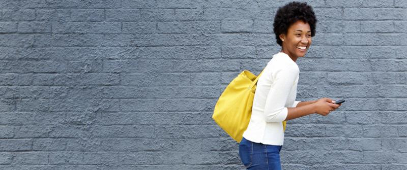 Photo fo a smiling woman carrying a yellow bag. She's walking in front of a gray brick wall and carrying her phone.