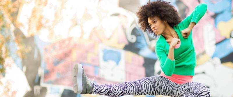 Photo of a woman wearing zebra-striped leggings jumping up and kicking in the style of kick boxing.