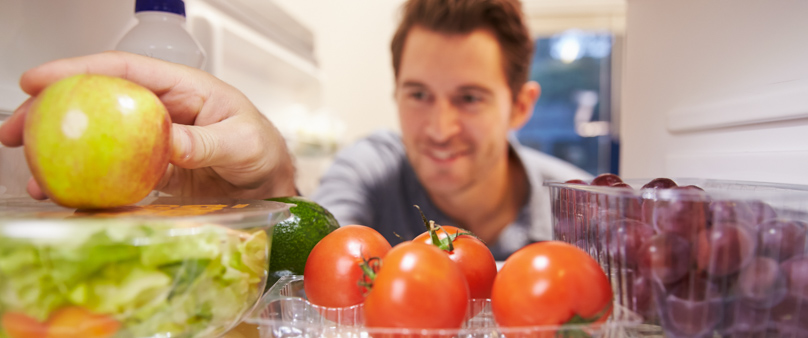 Photo of a man reaching into a fridge full of healthy fruits and vegetables, grabbing an apple.