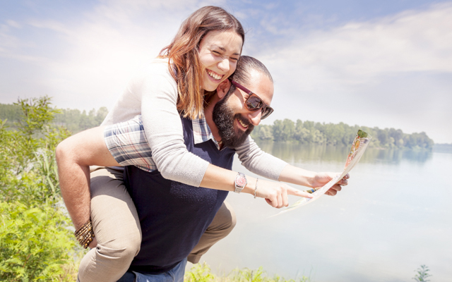 Photo of a smiling couple by a lake, a man holds a woman on his back while she holds out a map for them both to see