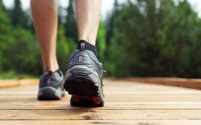 Photo of a pair of feet in tennis shoes walking across a wooden bridge with trees in the distance