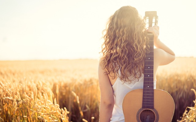 Photo of a woman facing away from the camera, looking out over a field as she holds an acoustic guitar over her shoulder