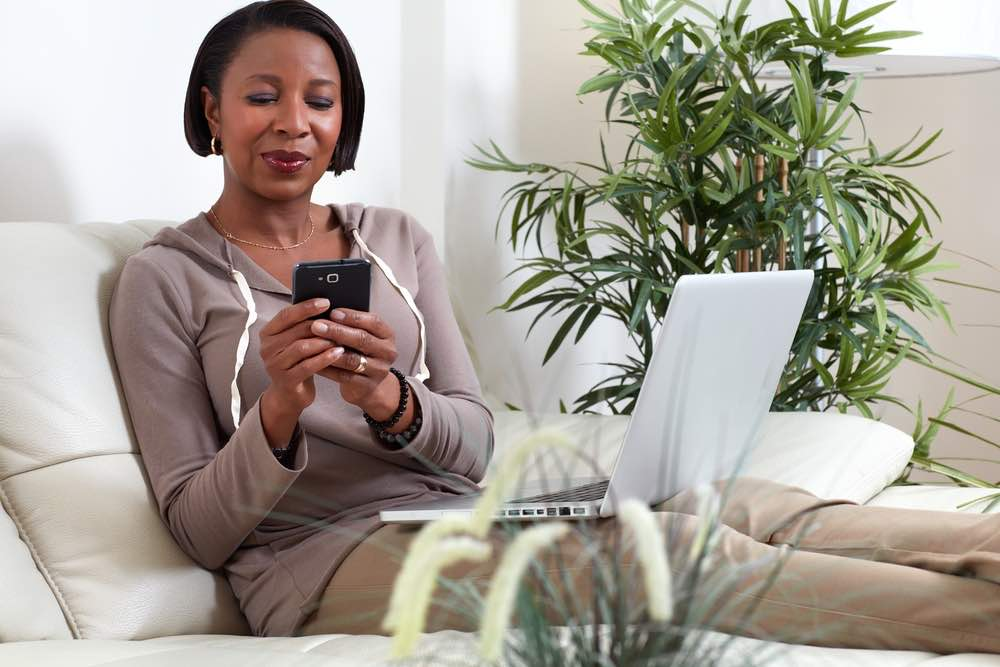 African American woman looking at phone at home