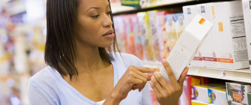 Photo of a woman in the store, examining the back of a package of food