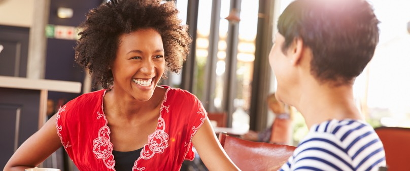 A photo of two women sit drinking coffee, smiling, and talking