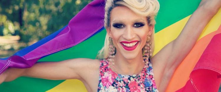 LGBT person holding up a rainbow pride flag and smiling