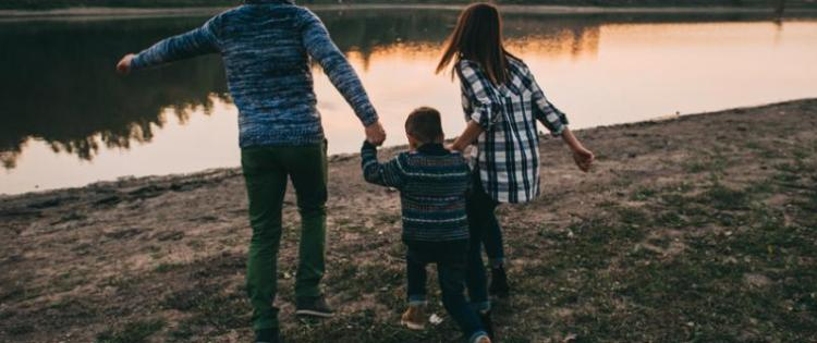 Photo of two adults with a child, walking towards a river and holding hands.
