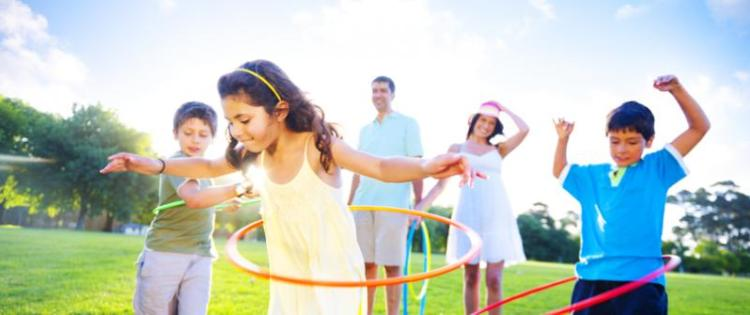 Photo of a mom, dad, and three kids in a park on a sunny day. The kids are playing with hula hoops.