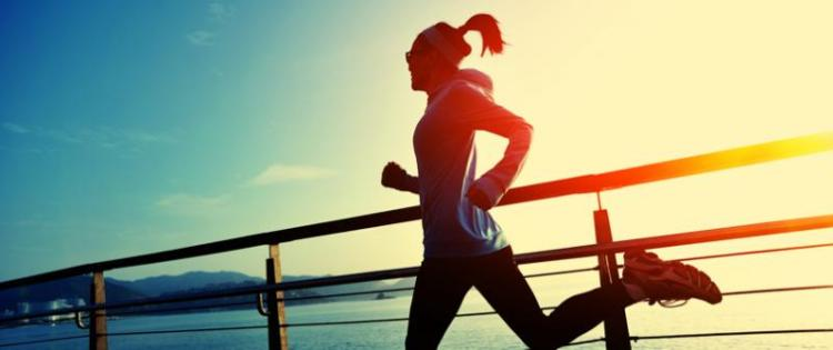 Photo of a woman jogging down a dock with water in the background. She is backlit by the rising sun.