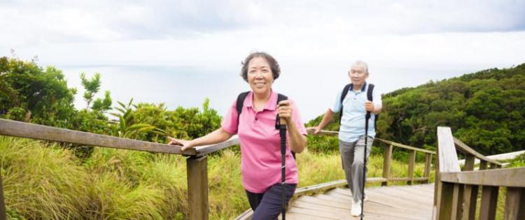 Photo of a senior couple walking up a gently sloped path.