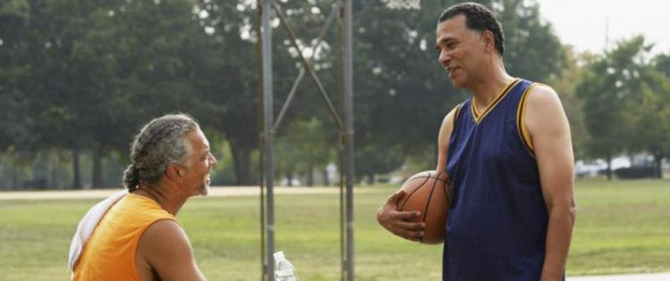 Photo of two men who have paused a 1-on-1 basketball game to talk