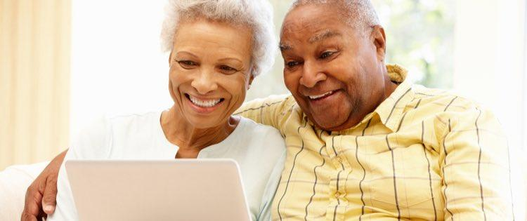 Senior african american couple using laptop happily