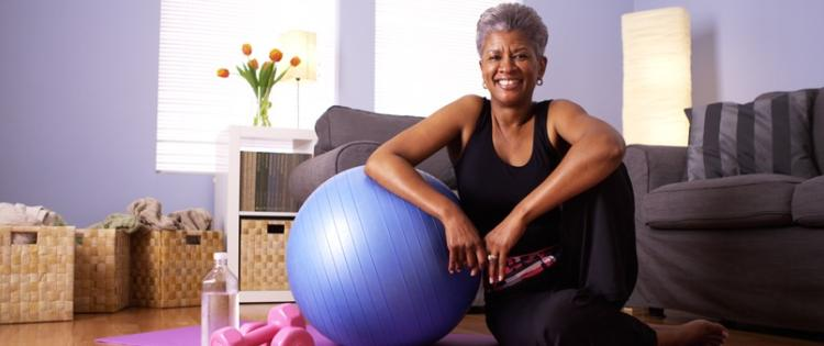 Photo of a woman in her home with water, an exercise ball, yoga mat, and light weights