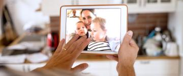 Person video chatting with woman and two children on a tablet device