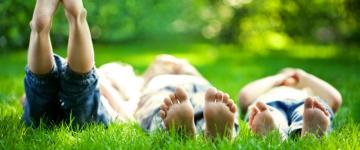 Photo of three kids lying barefoot in the grass. Their feet are close to the camera. One kid has his feet raised to the sky.