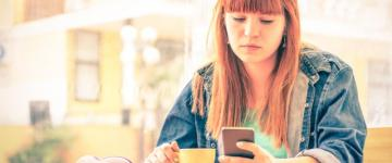 Photo of a serious young woman drinking coffee and staring at her phone.