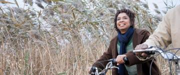 Photo of a woman on a bicycle in autumn, she wears a coat and scarf. A second cyclist can be partially seen to her side.