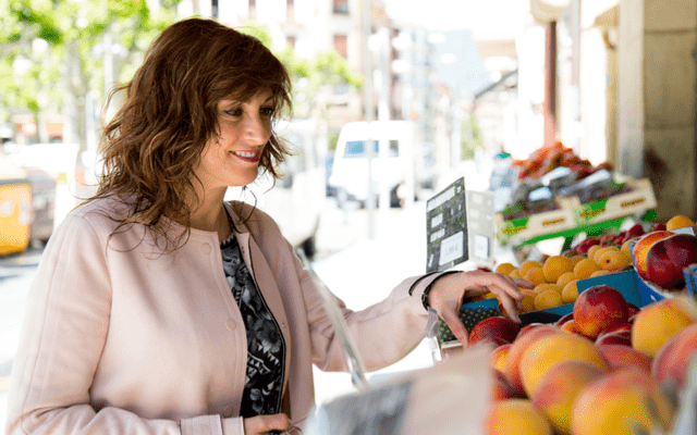 Photo of a woman shopping for nectarines at fruit stand