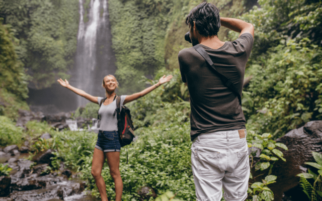 Photo of a man taking a picture of his blonde girlfriend near a waterfall in the jungle