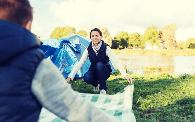 Photo of a woman opening a picnic blanket with a friend while at a campsite