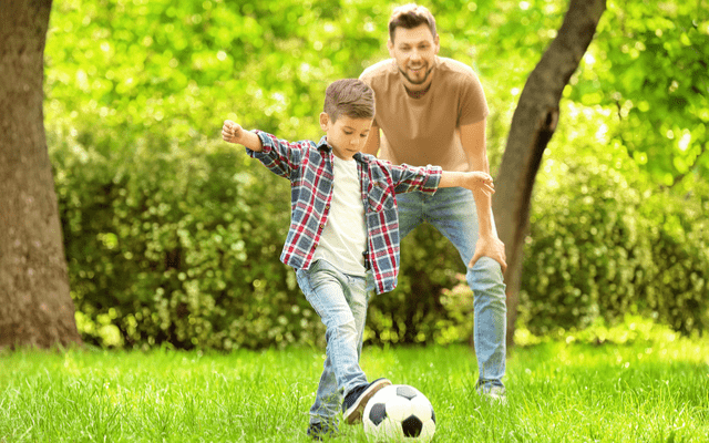 Photo of a young father playing soccer with his son at a park