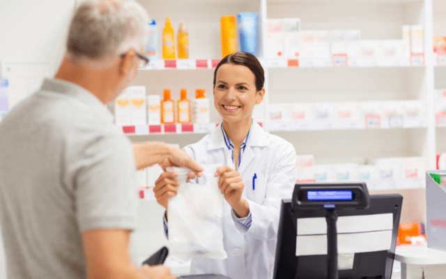 Photo of young female pharmacist handing a bag to an older man
