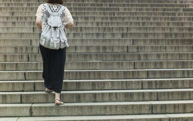Photo of a woman in a skirt, wearing a backpack and walking away from the camera up a flight of concrete stairs