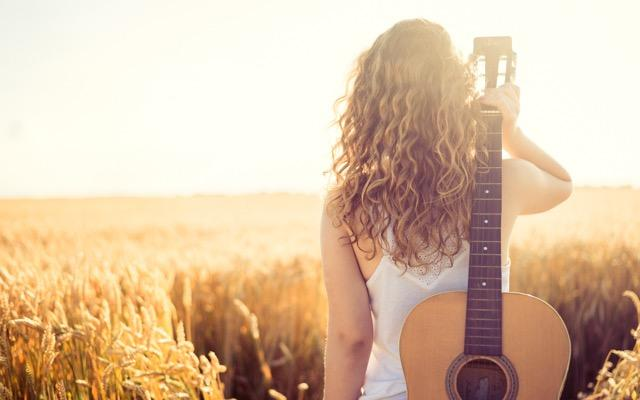 Photo of a woman facing away from the camera, looking out over a field as she holds an acoustic guitar over her shoulder.