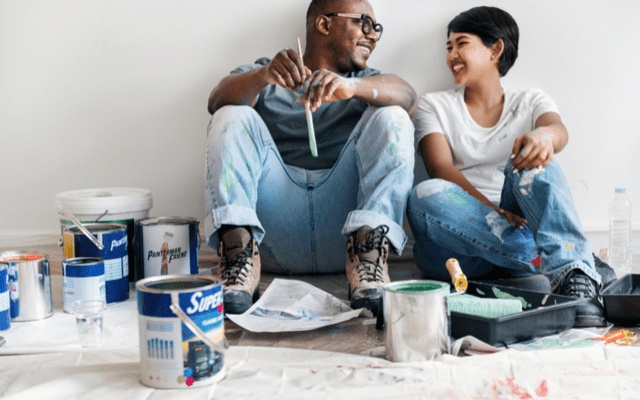 Photo of a young couple resting on the floor surrounded by painting supplies