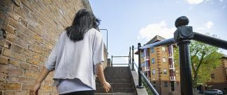 Photo of a woman with dark hair walking up outdoor stairs in a city