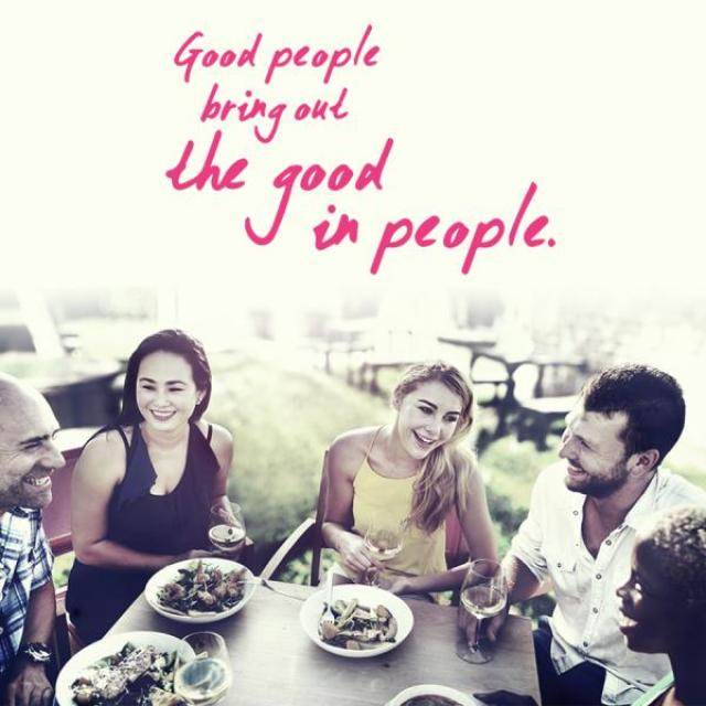 "Image of several people eating at a table and laughing together.  The caption reads, ""Good people bring out the good in people."""