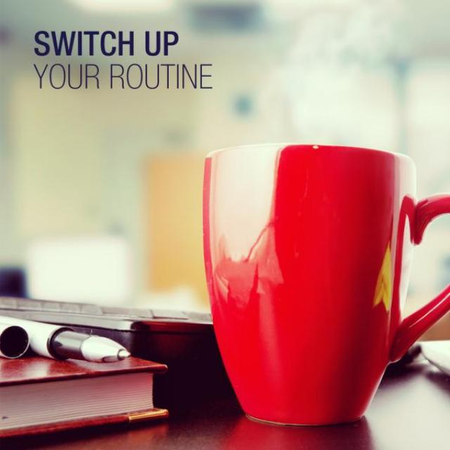 "A red coffee cup sits on a desk crowded with books. In the top corner it reads ""Switch up your routine."""