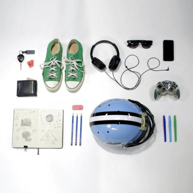 Lots of everyday objects are laid out on a white background. A wallet, car keys, a notebook, shoes, headphones sunglasses, pens and pencils, and even a video game controller are all set down in an orderly fashion.