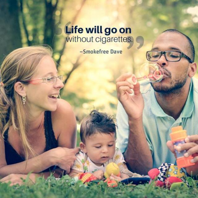 "A man and woman lay in the grass with a baby playing with toys between them. The man is blowing bubbles. The text overlay reads ""life will go on without cigarettes"" and is attributed to Smokefree Dave"