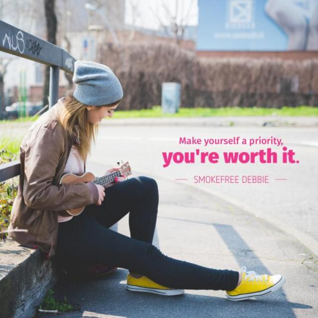 "A young girl sits on the side of the road playing the ukulele. The text says, ""Make yourself a priority, you're worth it"" and is attributed to Smokefree Debbie."