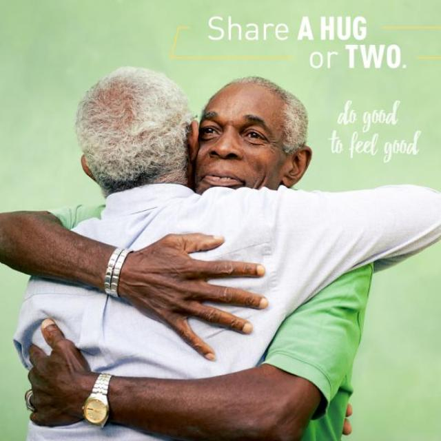 "Image of two older men hugging. The caption reads, ""Share a hug or two. Do good to feel good."""