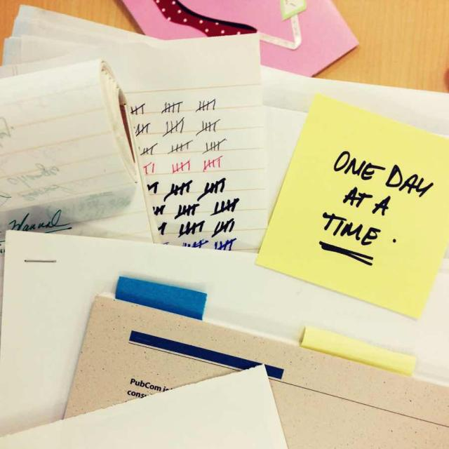 "Photo of a pile of papers with a post-it note saying ""One day at a time."""