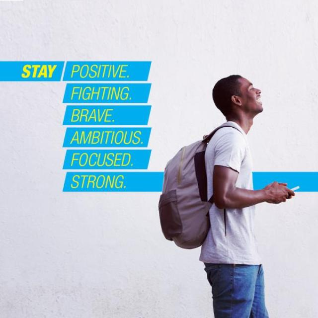 "A young man wearing a backpack laughs while looking at his phone. The text behind him reads ""Stay positive. Fighting. Brave. Ambitious. Focused. Strong."""